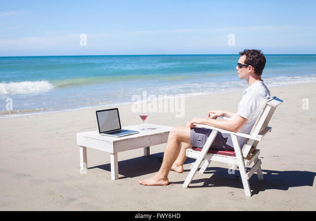 telecommuting, businessman relaxing on the beach with laptop and cocktail, freelancer workplace, dream job - Stock Image