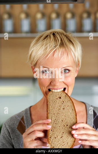 Mature woman with blond hair biting into a slice of bread, close-up - Stock Image