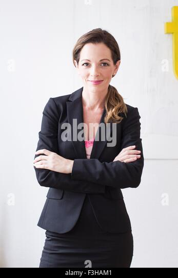 Mature woman wearing business attire arms crossed looking at camera smiling - Stock Image