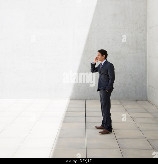 Businessman standing in shade and talking on cell phone - Stock Image