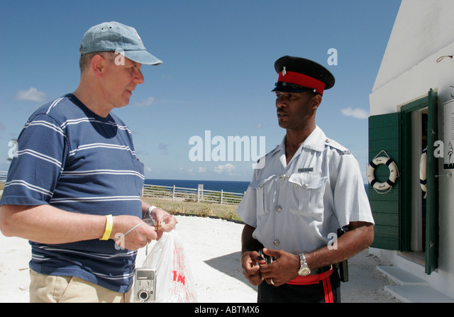 Turks and Caicos Grand Turk Lighthouse built 1852 North East Point Black male policeman helps tourist - Stock Image