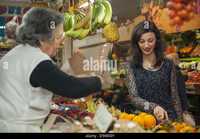 Woman shopping at greengrocer's in market - Stock Image