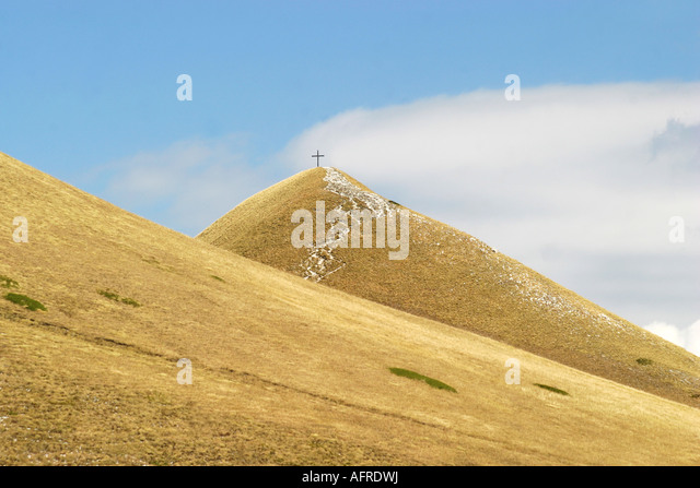 A Distant Cross tops Gloriously  coloured Sasso Tetto  mountain in the Sibillini National Park,Le Marche,The Marches, - Stock Image