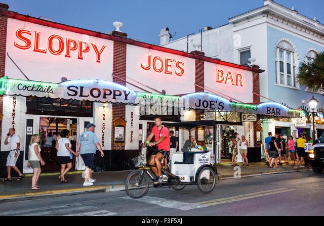 Key West Florida Keys Old Town Duval Street night nightlife Sloppy Joe's Bar front entrance pedicab - Stock Image