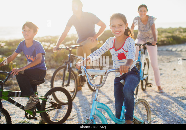 Family riding bicycles on sunny beach - Stock-Bilder