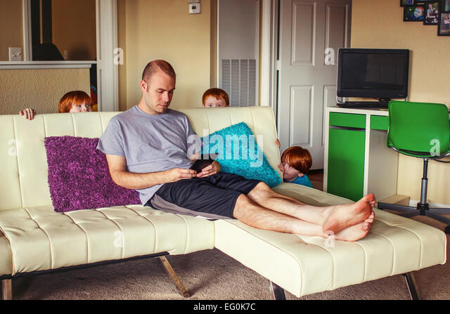 Three young boys hiding behind couch ready to surprise their father - Stock Image