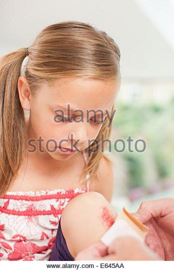 Close up of putting bandage on girl knee - Stock Image