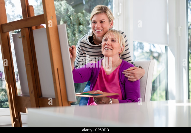 Family portrait with happy mother painting for hobby and daughter smiling and hugging her at home - Stock Image