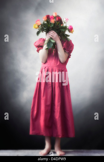 a girl in a red dress holding a bouquet of flowers in front of her face - Stock Image