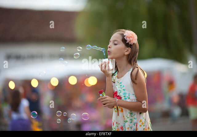 Girl (8-9) in dress blowing soap bubbles - Stock Image