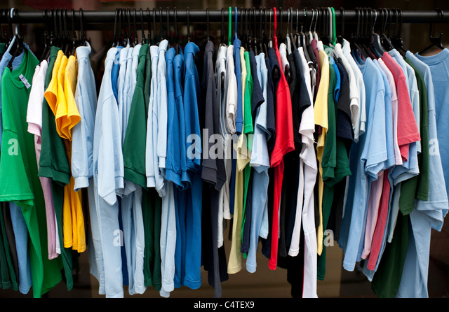 a rack of cheap polo shirts sports on sale, UK - Stock Image