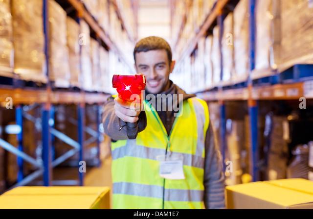 Worker holding scanner in warehouse - Stock-Bilder