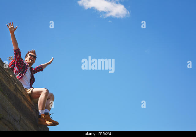 Happy tourist with raised arms sitting on cliff against blue sky - Stock Image