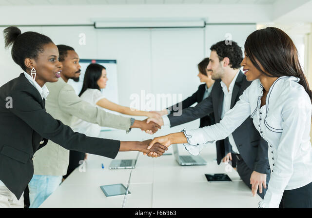 Business people shaking hands before sitting down to a conference table - Stock Image