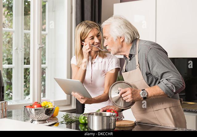 Senior man cooking with daughter, tasting food - Stock Image