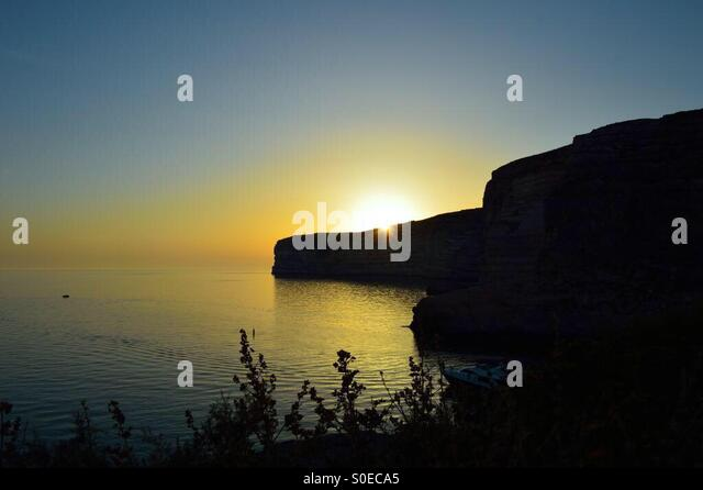 Sunset on Xlendi Bay in Gozo, Malta. - Stock Image
