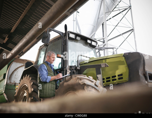 Farmer writing notes by tractor - Stock Image