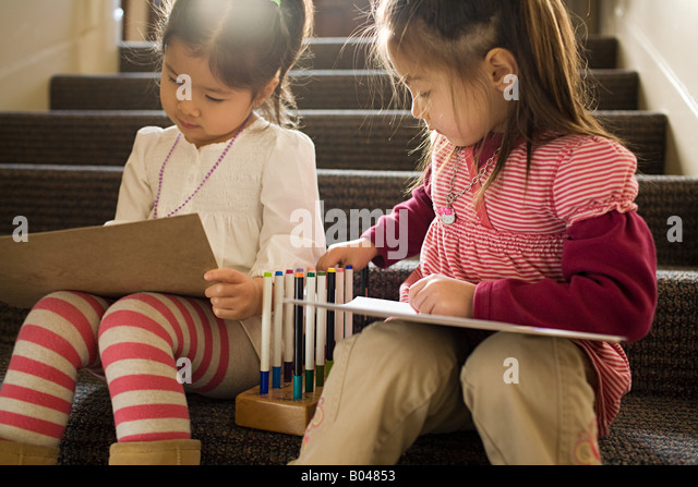 Girls sat on a step drawing - Stock Image