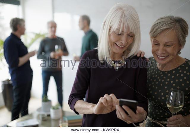 Smiling senior women texting with smart phone and drinking wine,enjoying social gathering - Stock Image