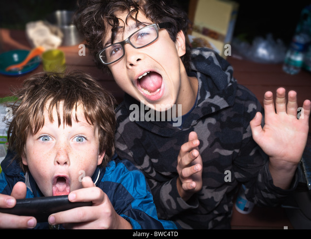 Boys excited by portable game system - Stock Image