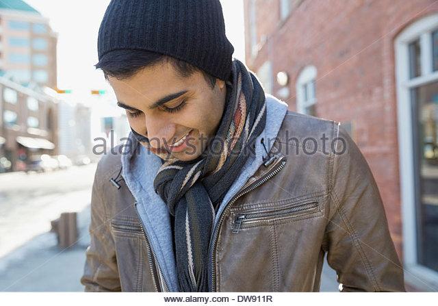 Smiling man standing outdoors looking down - Stock-Bilder