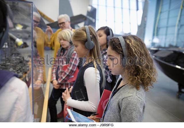 Curious students wearing headphones at exhibit on field trip in war museum - Stock-Bilder