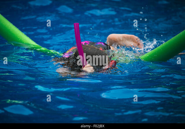 A girl swimming in a pool with goggles and a snorkel - Stock Image