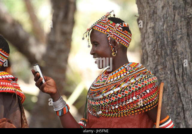 LOIYANGELENI, KENYA - May 18. A Samburu woman uses her mobile phone during the rehearsals of the Lake Turkana Festival - Stock Image