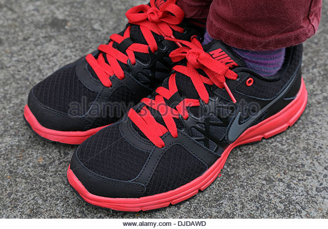 A boy wearing a new clean pair of red and black Nike shoes, Scotland,