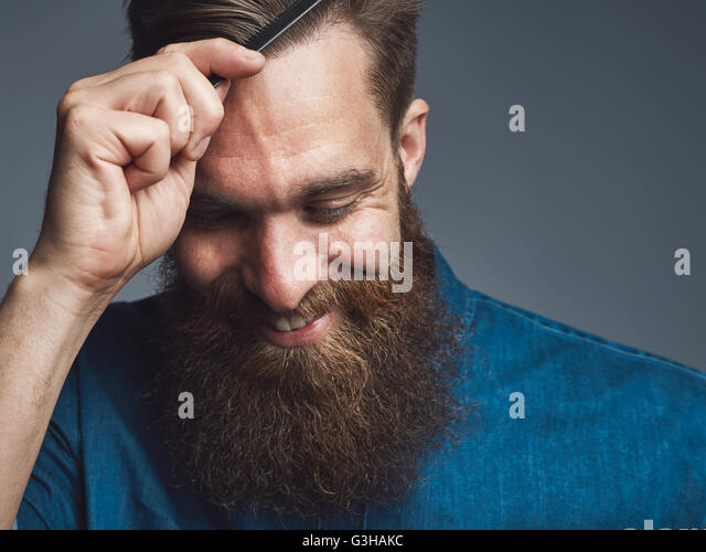 Well groomed handsome bearded man in blue denim shirt and happy expression combing his hair over gray background - Stock Image