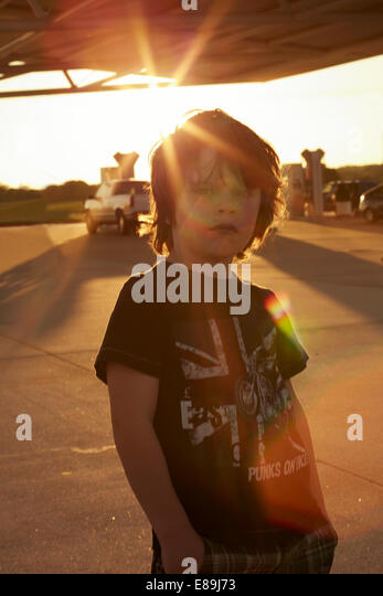 Boy standing at gas station at sunset - Stock-Bilder