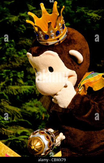 Portrait of Curious George cartoon character in Mardi Gras crown at Universal Studios Orlando - Stock Image