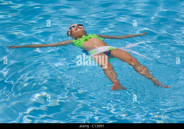 young girl floating in swimming pool - Stock Image