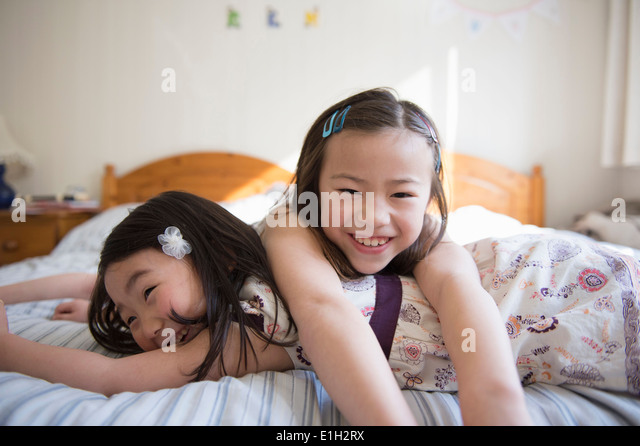 Two young female friends lying on bed - Stock Image