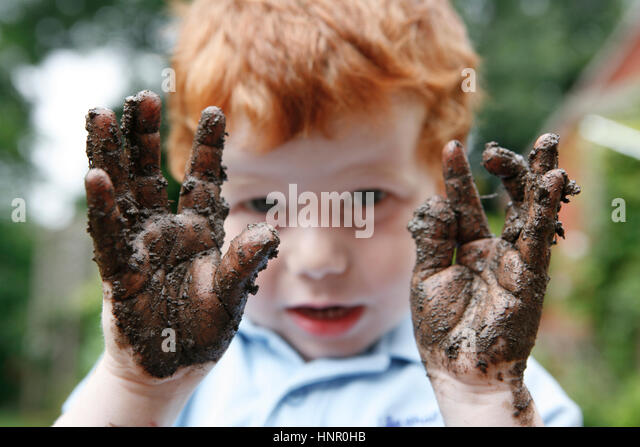 A child holding out his muddy hands - Stock Image