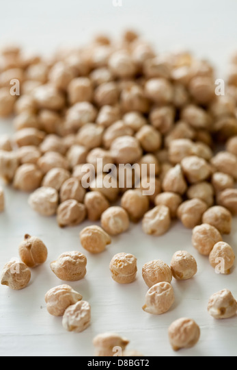 Closeup of a pile of uncooked chickpeas on a white table surface. - Stock Image