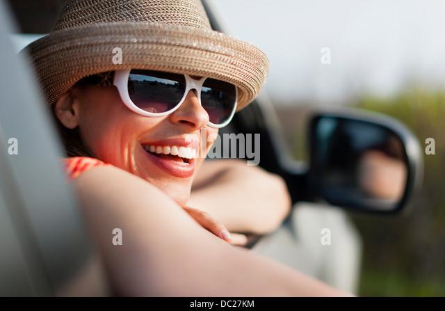 Mature woman wearing sunglasses and sunhat - Stock Image