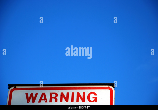 Warning sign against blue sky. - Stock Image