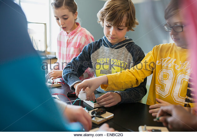 Students assembling circuit electronics at table - Stock Image