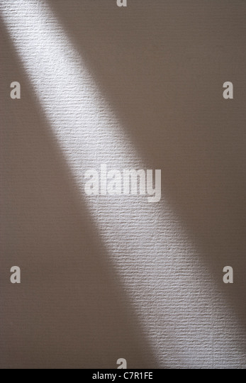 Shaft of light across white textured paper. - Stock Image