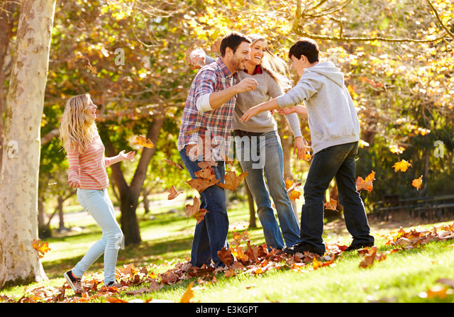 Family Throwing Autumn Leaves In The Air - Stock Image