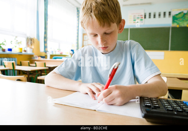 Boy studying in school - Stock Image