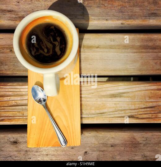 An  overhead shot of an Americano and a spoon on a wood serving plate on a wooden bench - Stock-Bilder