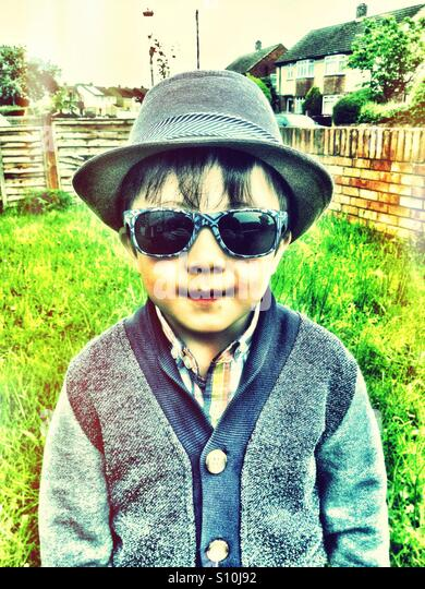A young boy wearing a hat and sunglasses. - Stock Image