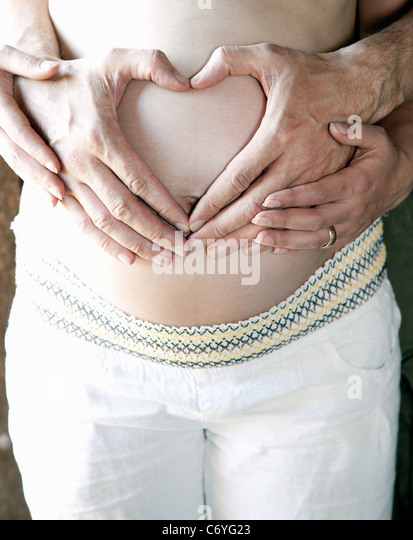 Couple holding woman's pregnant belly - Stock-Bilder