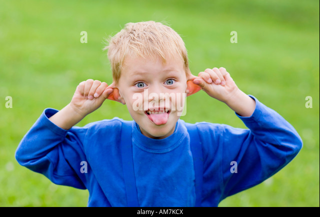 A boy, 5 years old, shows his tongue - Stock Image