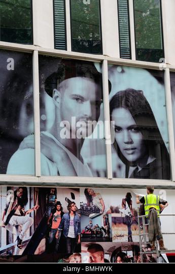 Man putting up posters billboards, Oxford Street, London, England, UK - Stock Image