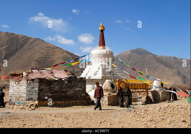 Tibetan Buddhism pirlgrims walk around a white stupa Kyi Chu valley Tibet China - Stock-Bilder