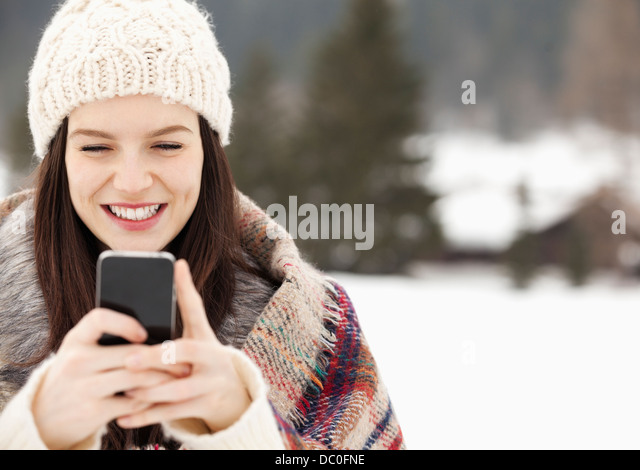 Close up of woman in knit hat text messaging with cell phone - Stock Image