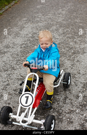 Toddler boy riding go-cart - Stock-Bilder